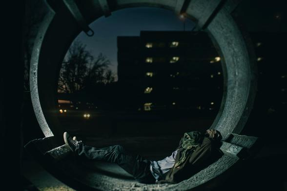 A man sleeping in a tunnel with his face covered.