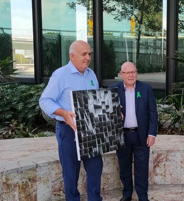 Two men holding an art print