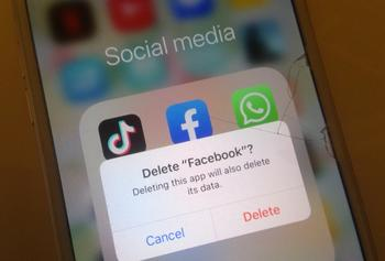 Image of a phone showing social media icons on the screen and a message saying delete facebook?