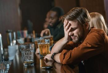 A person clutching his head at a bar.