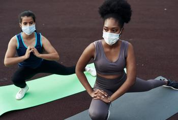 Two people doing yoga wearing facemasks.