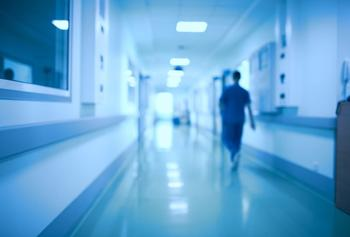 Blurred image of person walking down hospital corridor